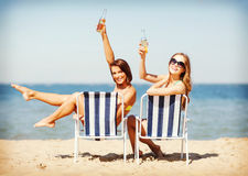 Muchachas que toman el sol en las sillas de playa Foto de archivo libre de regalías