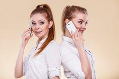 Muchachas que usan hablar del teléfono móvil Fotos de archivo