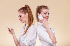 Muchachas que usan los teléfonos móviles que hablan el mensaje de la lectura Fotografía de archivo libre de regalías