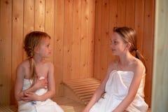 2 muchachas se están sentando en la sauna y están mirando uno a imagen de archivo