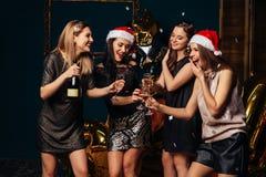 Muchachas sonrientes con champán en la fiesta de Navidad Imágenes de archivo libres de regalías