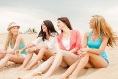 Muchachas sonrientes con las bebidas en la playa Imágenes de archivo libres de regalías