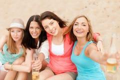 Muchachas sonrientes con las bebidas en la playa Imagen de archivo libre de regalías