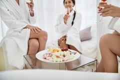 Muchachas sonrientes con las bebidas que se sientan cerca de la tabla con los dulces imagenes de archivo