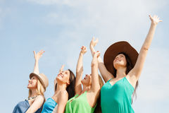 Muchachas sonrientes con las manos para arriba en la playa Foto de archivo libre de regalías