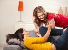 Muchachas sonrientes con los auriculares en el sofá Imágenes de archivo libres de regalías