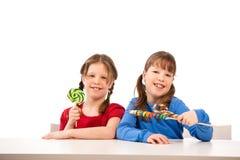 Muchachas sonrientes con los lollipops Foto de archivo libre de regalías