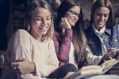 Muchachas sonrientes de los estudiantes que aprenden junto foto de archivo