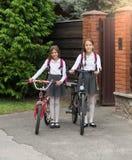 Muchachas sonrientes en uniforme escolar con las bicicletas delante de la casa Foto de archivo