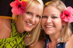Muchachas sonrientes hermosas con la flor del hibisco Fotos de archivo libres de regalías