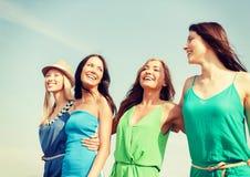 Muchachas sonrientes que caminan en la playa Imagen de archivo libre de regalías