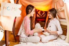 Muchachas sonrientes que juegan en la casa hecha de mantas en el dormitorio Foto de archivo