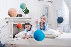 Muchachas sonrientes que miran modelos de los planetas Fotografía de archivo