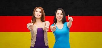 Muchachas sonrientes que muestran los pulgares para arriba sobre bandera alemana Imágenes de archivo libres de regalías