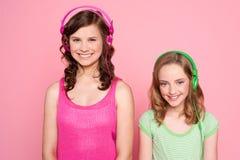 Muchachas sonrientes que presentan con el auricular Fotos de archivo