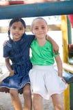 Muchachas sonrientes que se sientan en el gimnasio de selva en el patio Imágenes de archivo libres de regalías