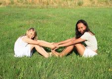Muchachas sonrientes que se sientan en hierba Foto de archivo libre de regalías