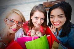 Muchachas sonrientes que sostienen bolsos de compras Imagen de archivo libre de regalías