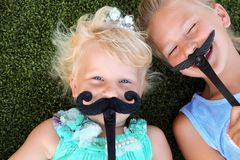 Muchachas sonrientes rubias hermosas que mienten en la hierba en un día de verano con el bigote imagen de archivo