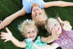 Muchachas sonrientes rubias hermosas que ponen en la hierba en un día de verano imagenes de archivo