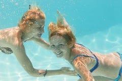 Muchachas subacuáticas en thepool Imagenes de archivo