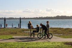 Muchachas Teenaged en una mesa de picnic hacia fuera por el agua en el sábado a última hora de la tarde en Redlands Queensland Au Fotos de archivo libres de regalías
