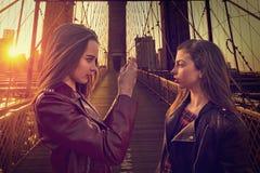 Muchachas turísticas adolescentes que toman la foto en el puente de Brooklyn NY imagen de archivo