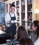 Muchachas y camarero en café Fotografía de archivo libre de regalías