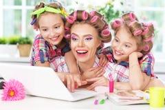 Muchachas y madre en bigudíes de pelo con el ordenador portátil Foto de archivo