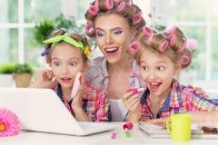 Muchachas y madre en bigudíes de pelo con el ordenador portátil Fotografía de archivo