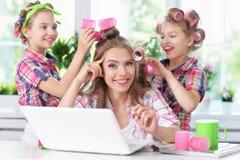 Muchachas y madre en bigudíes de pelo con el ordenador portátil Fotos de archivo