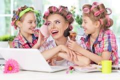 Muchachas y madre en bigudíes de pelo con el ordenador portátil Foto de archivo libre de regalías