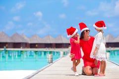 Muchachas y mamá de Littlw en el sombrero de Papá Noel el días de fiesta de la Navidad Imagen de archivo