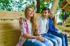 Muchachas y muchacho sonrientes que se divierten en el patio Niños que juegan al aire libre en verano Adolescentes en un oscilaci Fotos de archivo