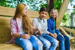 Muchachas y muchacho sonrientes que se divierten en el patio Niños que juegan al aire libre en verano Adolescentes en un oscilaci Foto de archivo libre de regalías