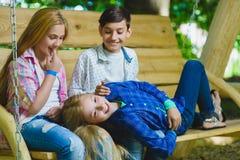 Muchachas y muchacho sonrientes que se divierten en el patio Niños que juegan al aire libre en verano Adolescentes en un oscilaci Fotografía de archivo libre de regalías