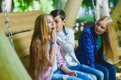 Muchachas y muchacho sonrientes que se divierten en el patio Niños que juegan al aire libre en verano Adolescentes en un oscilaci Imágenes de archivo libres de regalías