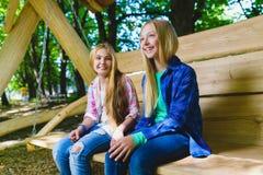 Muchachas y muchacho sonrientes que se divierten en el patio Niños que juegan al aire libre en verano Adolescentes en un oscilaci Foto de archivo