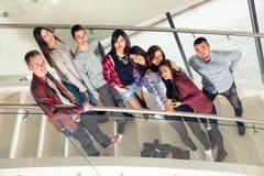 Muchachas y muchachos adolescentes felices en las escaleras escuela o universidad Foto de archivo libre de regalías