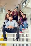 Muchachas y muchachos adolescentes felices en las escaleras escuela o universidad Imágenes de archivo libres de regalías