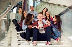 Muchachas y muchachos adolescentes felices en las escaleras escuela o universidad Imagen de archivo libre de regalías
