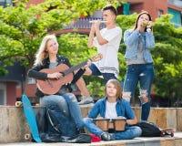 Muchachas y muchachos de risa con los instrumentos musicales Foto de archivo
