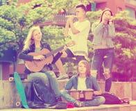 Muchachas y muchachos de risa con los instrumentos musicales Imágenes de archivo libres de regalías
