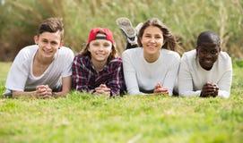 Muchachas y muchachos que presentan en parque de la primavera Foto de archivo