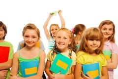 Muchachas y muchachos sonrientes que sostienen los libros de texto Imagen de archivo