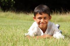 Muchacho étnico joven que miente en la hierba en parque Foto de archivo
