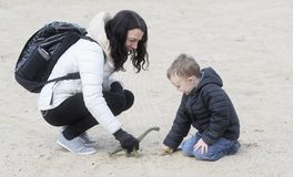 Muchacho año cuatro que juega en la playa y la arena con su madre y dinosaurios en tiempo del invierno foto de archivo libre de regalías