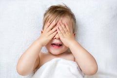 Muchacho año dos que cubre su cara con jugar de las manos foto de archivo