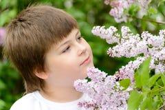 Muchacho 10 años de lilas florecientes cercanas Fotos de archivo libres de regalías