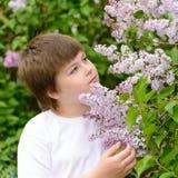 Muchacho 10 años de lilas florecientes cercanas Foto de archivo